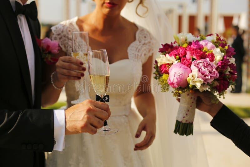 华美的拿着玻璃的新娘和新郎 免版税库存图片