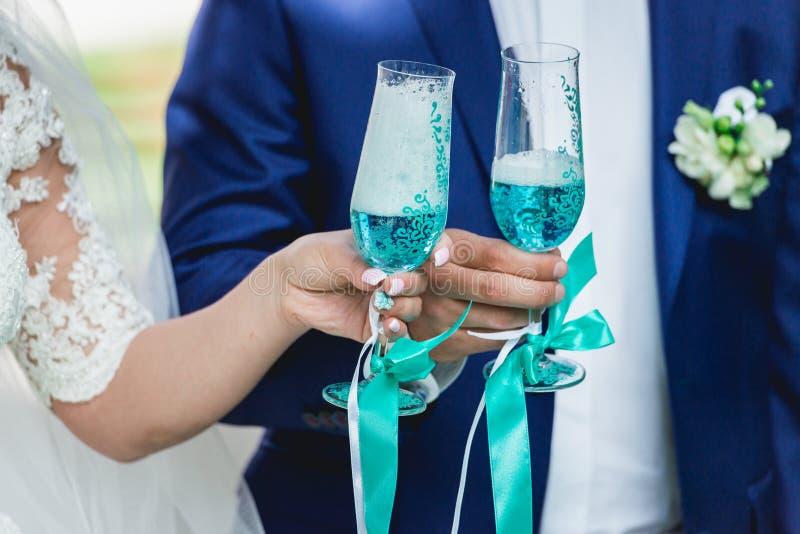 华美的敬酒用香槟,婚姻的早晨的新娘和新郎 拿着时髦的杯蓝色酒的手 免版税库存图片