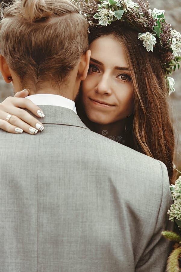 华美的新娘和时髦groomhugging激动, boho婚姻 图库摄影