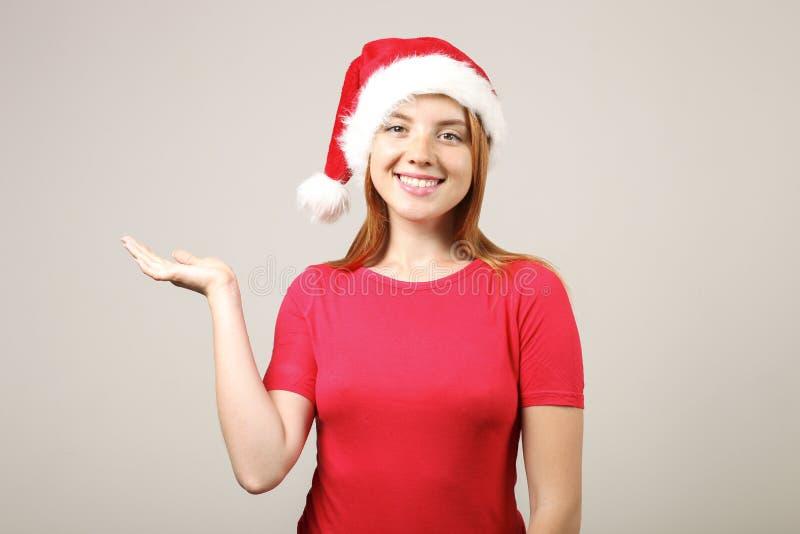 华美的有流行音乐pom的红头发人女性佩带的圣诞老人` s帽子,庆祝冬天欢乐季节假日 库存图片