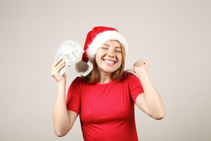 华美的有流行音乐pom的红头发人女性佩带的圣诞老人` s帽子,庆祝冬天欢乐季节假日 库存照片