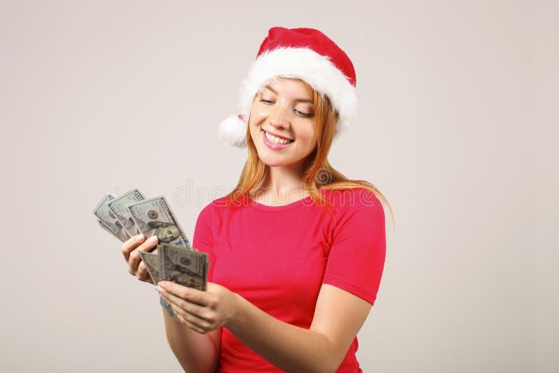 华美的有流行音乐pom的红头发人女性佩带的圣诞老人` s帽子,庆祝冬天欢乐季节假日 图库摄影