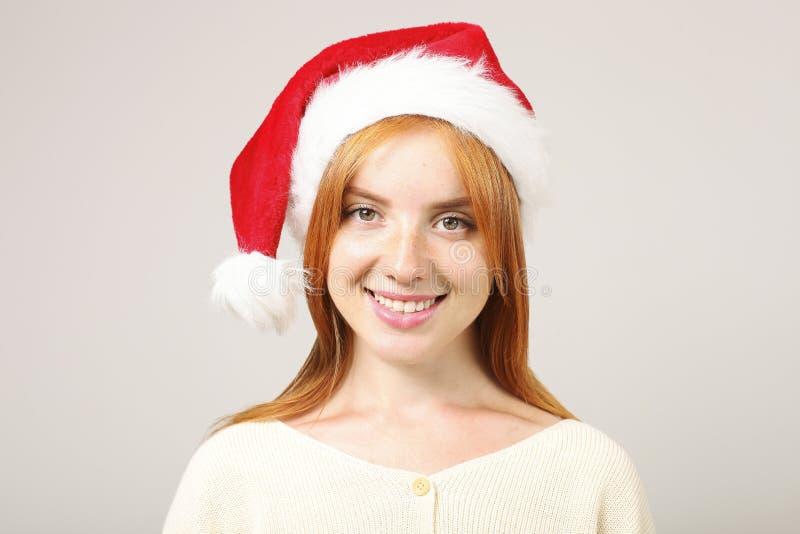 华美的有流行音乐pom的红头发人女性佩带的圣诞老人` s帽子,庆祝冬天欢乐季节假日 免版税库存图片
