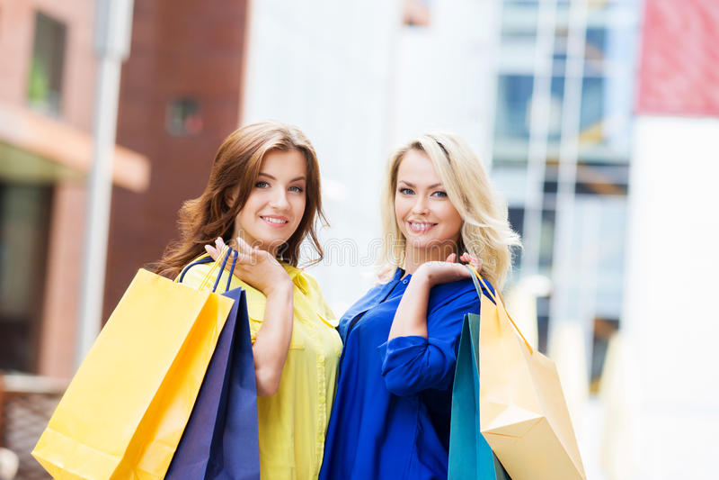 华美的浅黑肤色的男人和白肤金发满意对购物袋 图库摄影