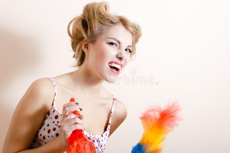 华美的白肤金发的相当滑稽的获得女孩年轻性感的画报的妇女乐趣清扫,表达战斗取消尘土&看照相机 免版税库存照片