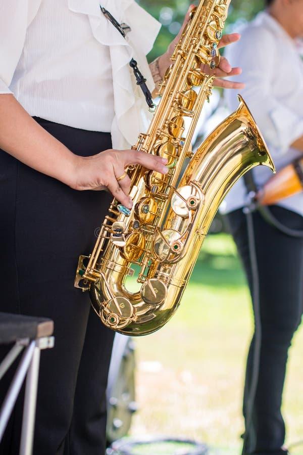 华美的萨克斯管吹奏者夫人弹在婚礼的萨克斯管 音乐家妇女 有吸引力的妇女和乐器 免版税库存图片
