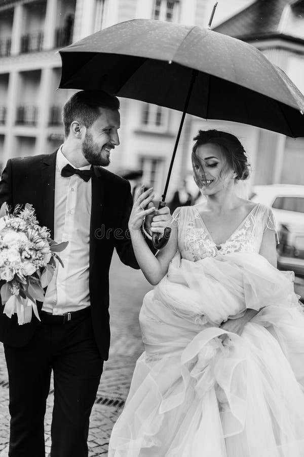 华美的走在多雨的伞下的新娘和时髦的新郎 免版税库存图片