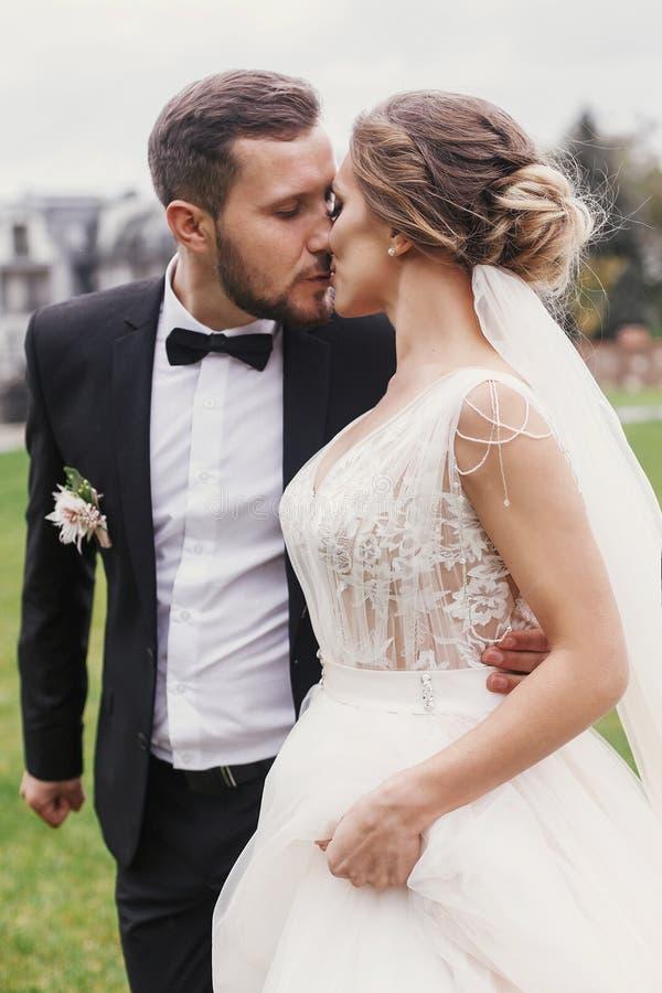 华美的轻轻地拥抱和亲吻outd的新娘和时髦的新郎 免版税库存照片