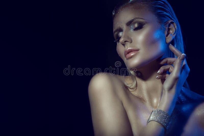 华美的迷人的白肤金发的妇女画象有湿头发、艺术性的闪烁的接触她的脖子的构成和赤裸肩膀的 免版税库存照片