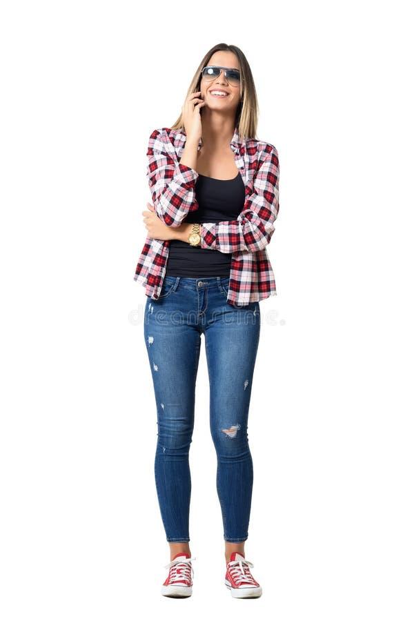 华美的年轻偶然笑妇女佩带的太阳镜,当谈话在手机时 图库摄影