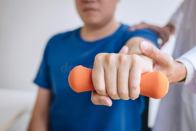 协助一名男性患者的医生生理治疗师,当给行使在舒展他的胳膊的治疗有在时的哑铃的 图库摄影