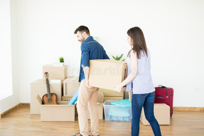 协助人的妇女运载重的箱子,当移动议院时 免版税库存照片