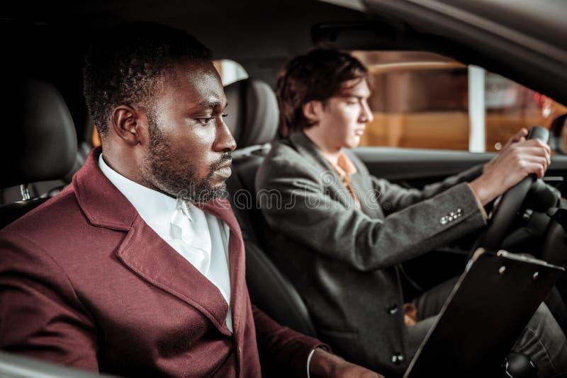 协助他的年轻客户的非裔美国人的驾驶的老师 库存图片