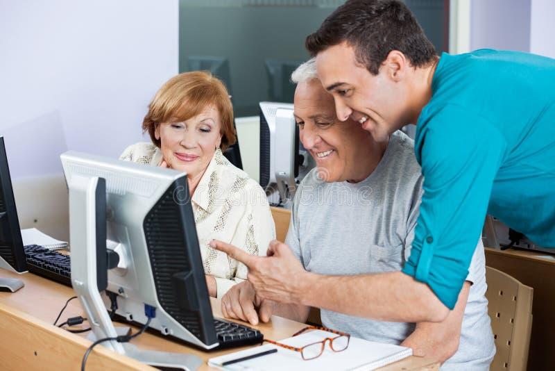 协助使用的家庭教师计算机资深学生在类 图库摄影