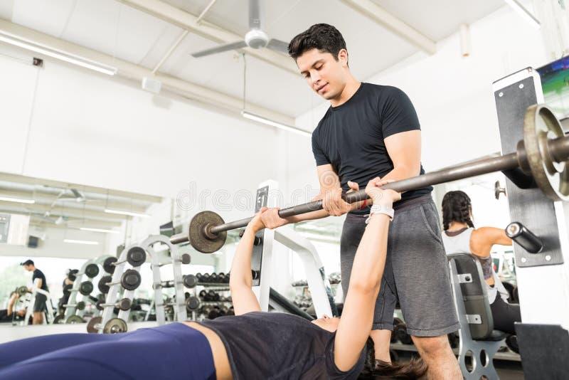 协助做的教练员卧推女性客户在健身房 图库摄影