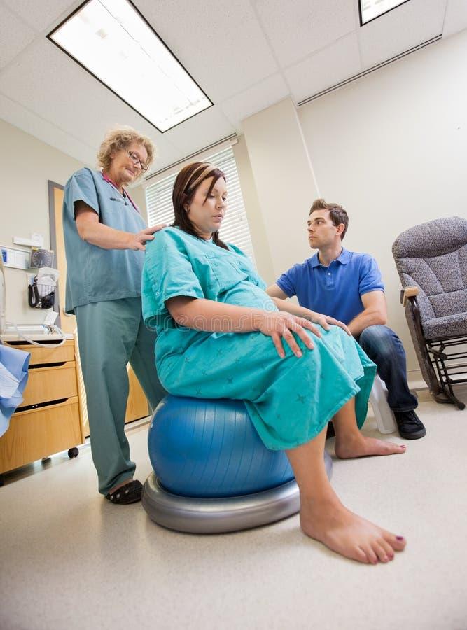 协助孕妇的护士坐彼拉多 免版税库存照片