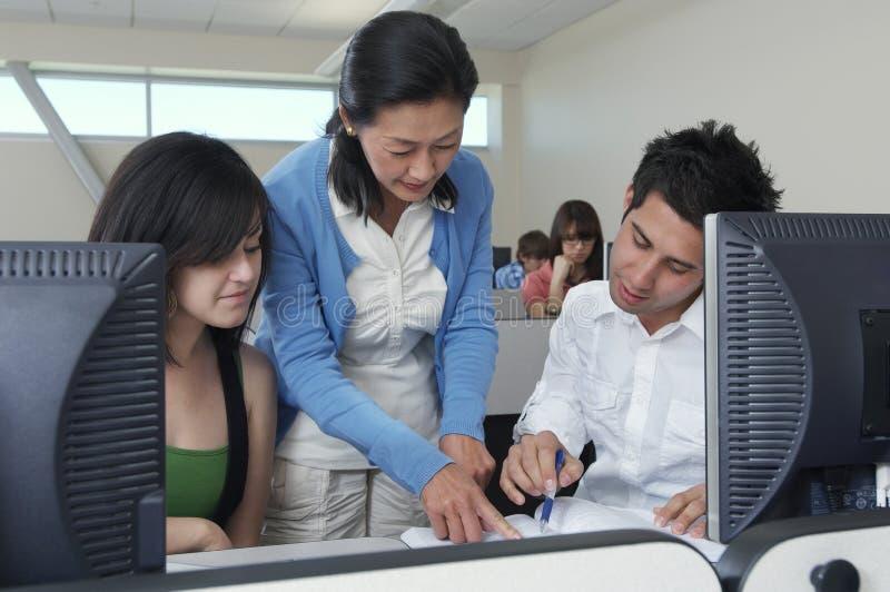 协助学生的老师在计算机实验室 库存照片
