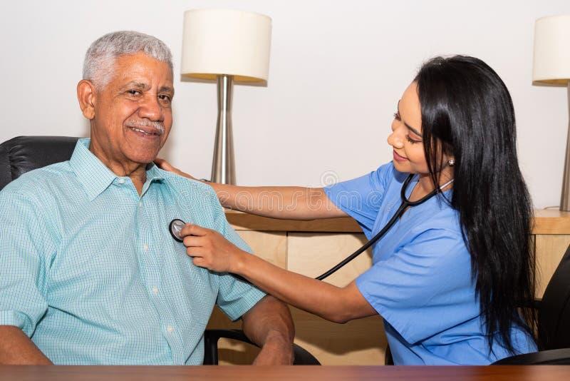 协助年长患者的家庭卫生保健护士 库存图片