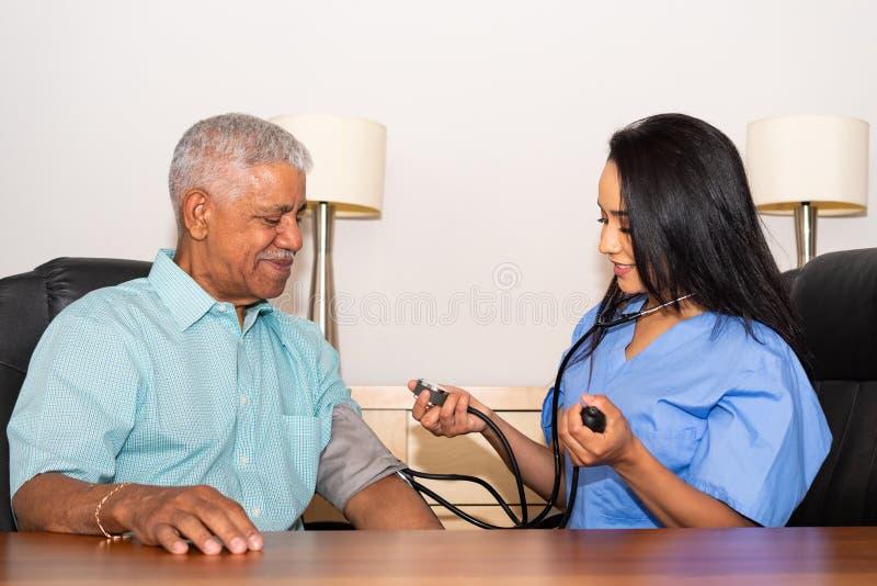 协助年长患者的家庭卫生保健护士 库存照片