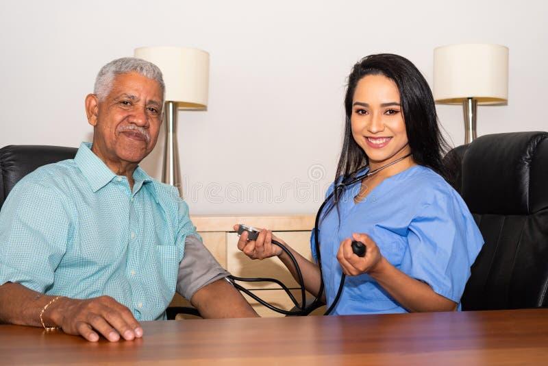 协助年长患者的家庭卫生保健护士 免版税图库摄影