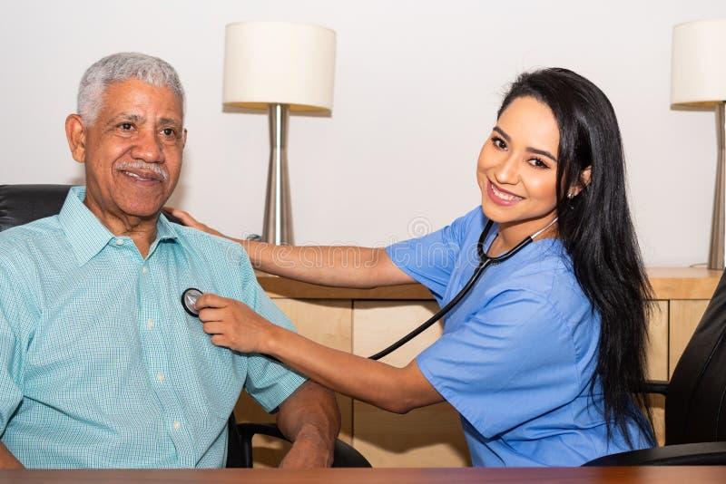 协助年长患者的家庭卫生保健护士 免版税库存图片