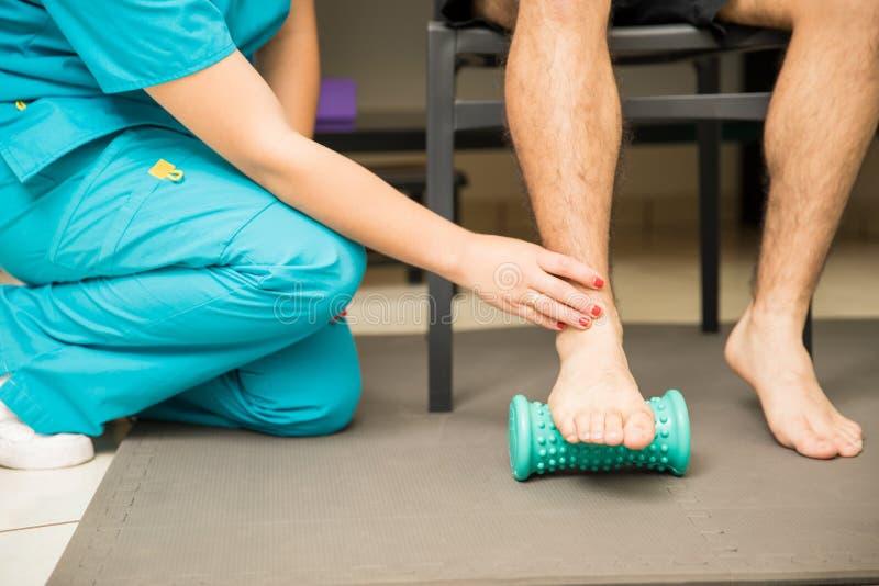 协助患者的治疗师为脚底Fasci使用脚路辗 图库摄影