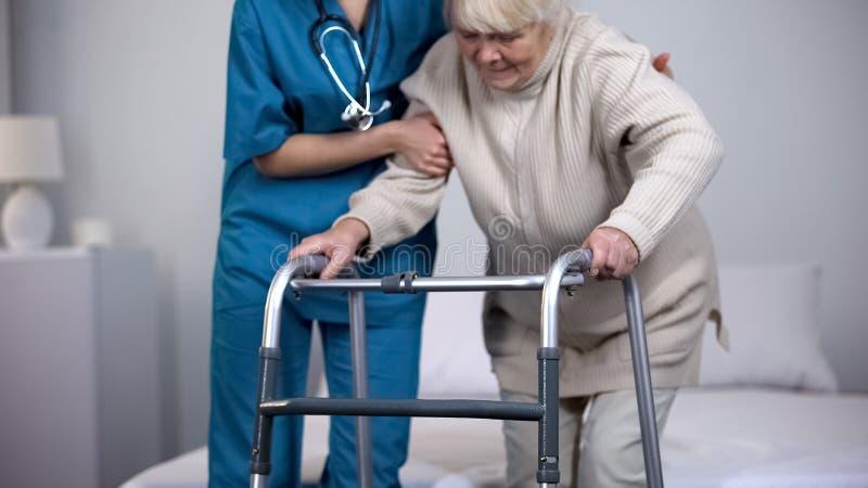 协助患者走的框架,上弦与斜端杆结点替换修复的护士 库存照片