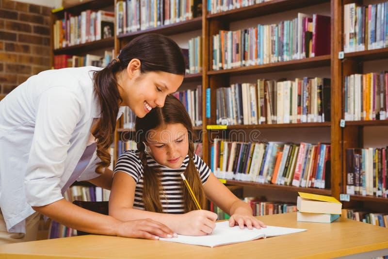 协助有家庭作业的老师女孩在图书馆里 库存图片