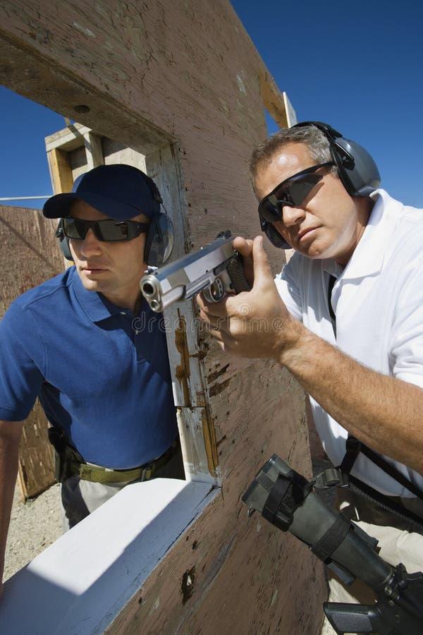 协助有手枪的辅导员人 免版税库存照片
