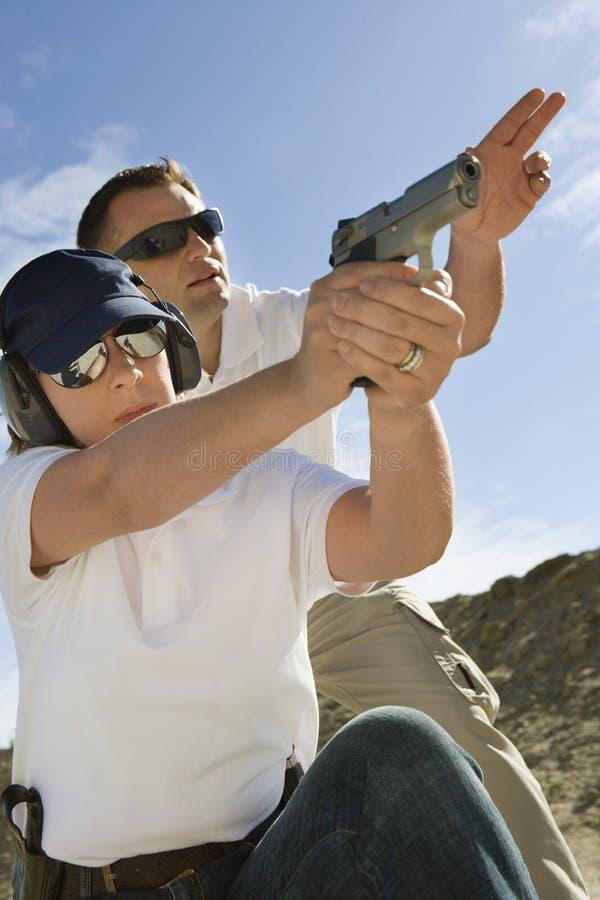 协助有手枪的辅导员妇女在射击距离 库存照片