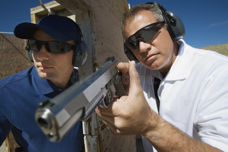 协助有手枪的辅导员官员 库存照片