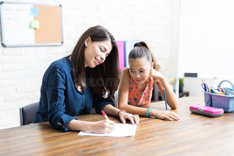 协助有Schoolwork的母亲女儿在表上 免版税库存图片