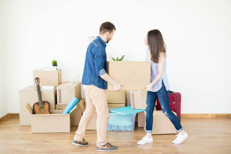 协助的夫妇在运载的箱子在新的家 库存图片
