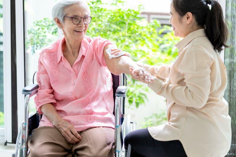 协助磨擦的女性照料者或孙女资深妇女身体干燥对安心热病或擦干净身体,亚洲人年轻人 免版税库存照片