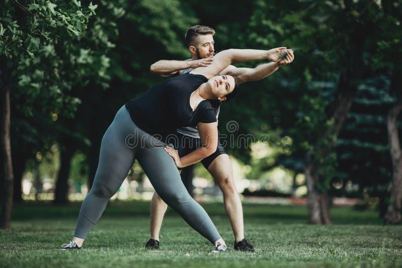 协助肥胖妇女行使的个人教练员 图库摄影