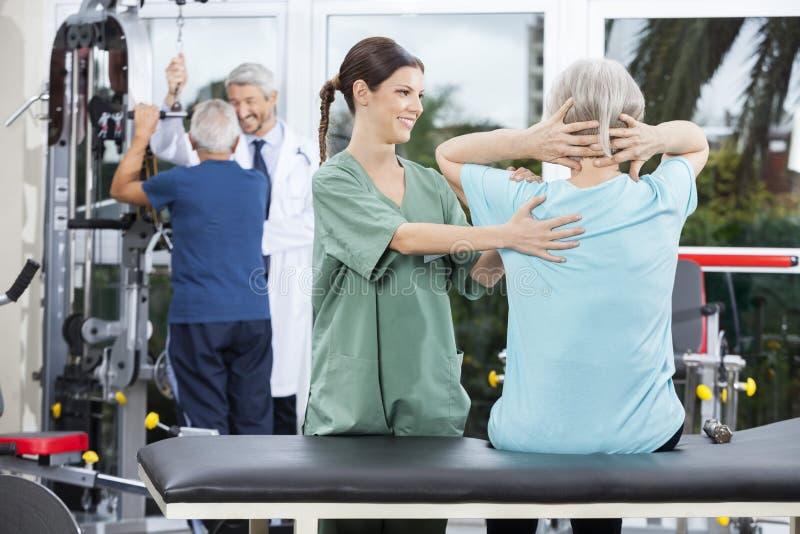 协助背部锻炼的护士资深妇女在康复中心 免版税库存图片