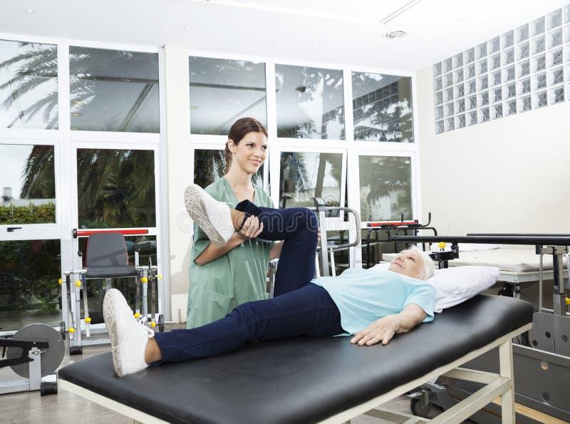 协助腿部锻炼的护士资深妇女在康复中心 免版税库存图片