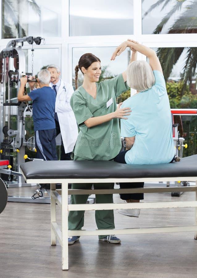 协助臂跑的护士资深妇女在康复中心 免版税图库摄影