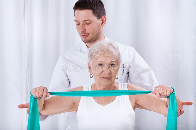 协助行使的Physiotheraqpist年长妇女 免版税库存照片