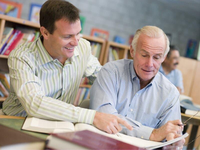 协助解决图书馆成熟学员家庭教师 免版税库存图片