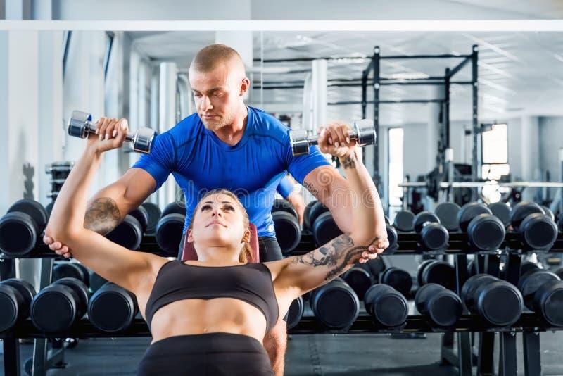 协助,当锻炼在健身房时的个人教练员 免版税库存图片