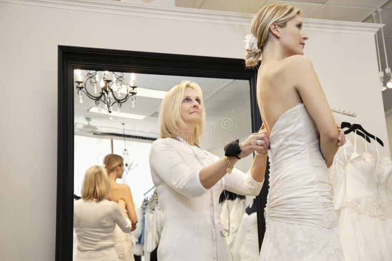 协助年轻新娘的资深所有者换衣服在婚礼服 库存图片