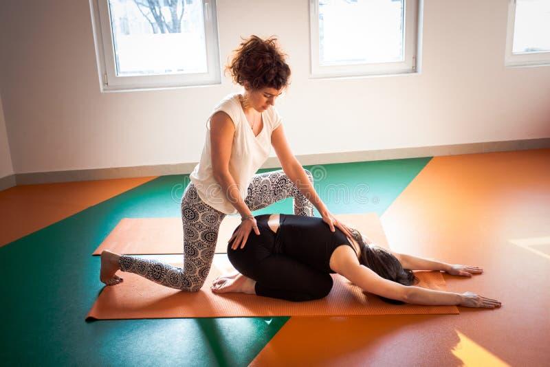协助锻炼的瑜伽辅导员学生 免版税库存照片