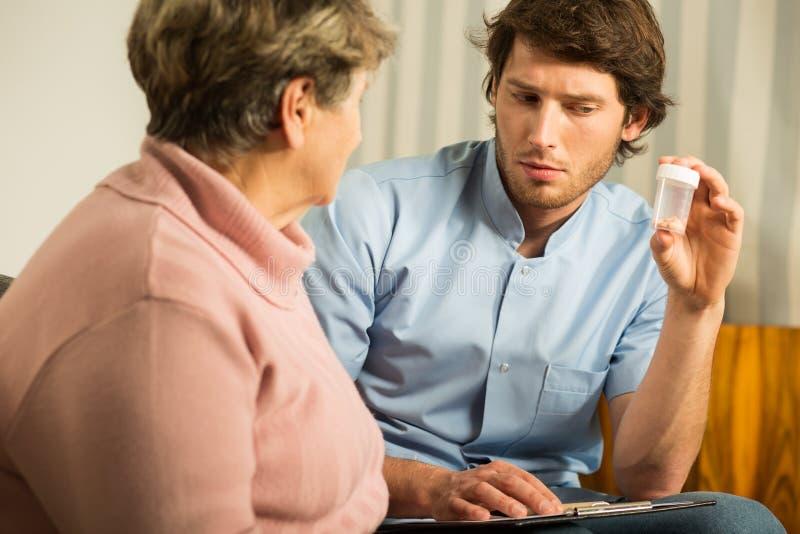 协助年长女性的年轻人 免版税库存照片
