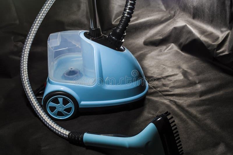 协定,蓝色房子的小吸尘器  清洁 设备 现代技术 黑色背景 库存图片