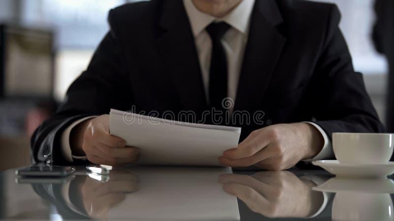 协议的年轻商人读书条款签字的,企业合同 免版税库存图片
