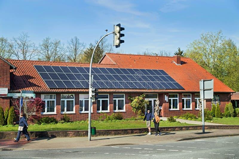 卑尔根,德国- 2017年4月30日:在一个房子屋顶的太阳能盘区在蓝天背景 库存照片