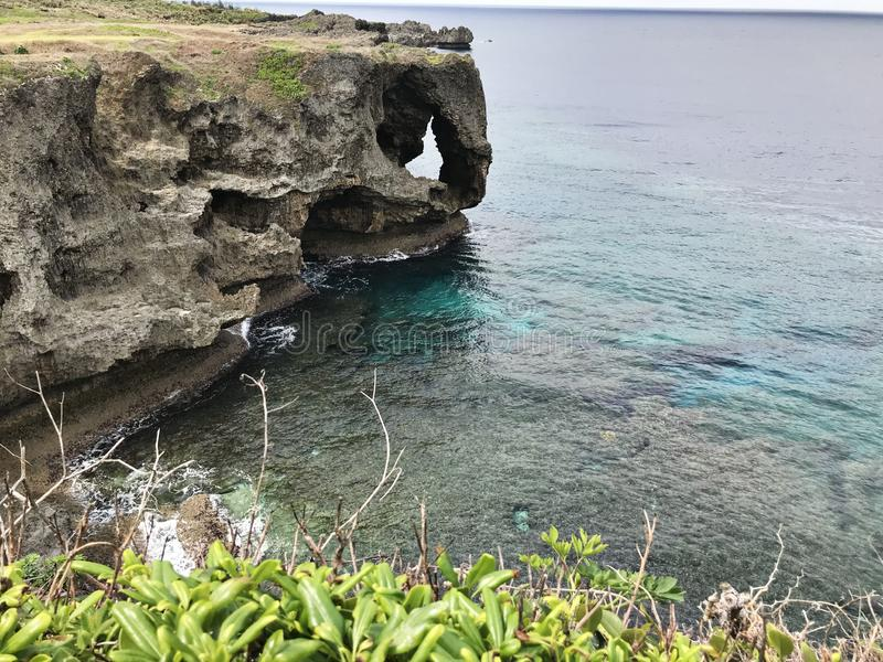 卓著的峭壁和鲜绿色海洋使目炫视图海角的Manzamo在日本 免版税库存照片