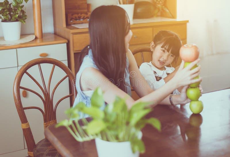 单亲母亲和一点女儿获得与新鲜水果一起在家厨房的乐趣早晨 免版税图库摄影