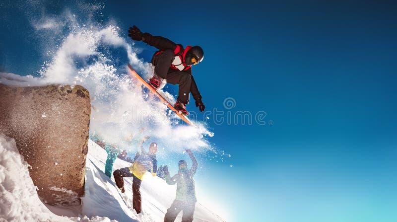单板滑雪者从大岩石跳向 免版税图库摄影